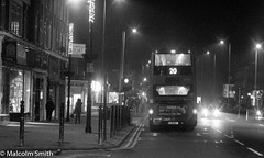 Route 20 Loughton (M C Smith) Tags: monochrome bw pentax kp bus route 20 shops trafficlights road pavement people lights letters numbers signs lines arrow bollards lamps women bag