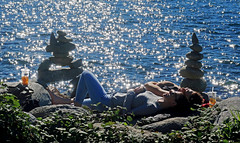 Words of Love by the Ocean (HereInVancouver) Tags: outdoors city rocks sculptures rockpiles woman love romance conversation candid streetphotography water reflection ocean pacific englishbay vancouverswestend thingstodobythewater bright canong9x vancouver bc canada