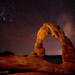 Delicate Arch at night with the lights of Moab