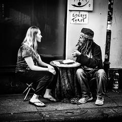 Energy Transfer (Kieron Ellis) Tags: man woman tarot energy sitting stool table ring hat divination water window wall pavement candid street blackandwhite blackwhite monochrome
