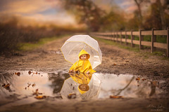 Baby with Umbrella ({jessica drossin}) Tags: jessicadrossin portrait toddler child kid rain slicker coat yellow fence road dirt puddle reflection baby wwwjessicadrossincom
