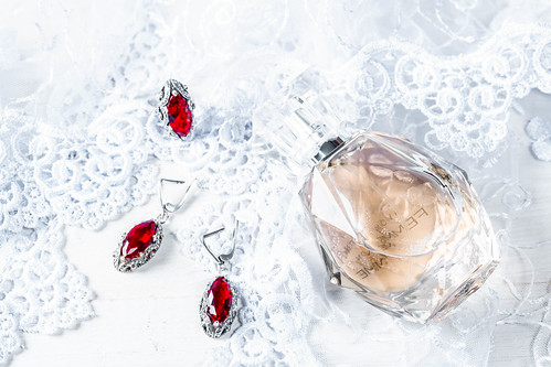 Perfume, earrings and ring with rubies on lace fabric
