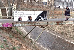 Advertisement (DJ_Black_Tea) Tags: advertisement billboard bridge rust oldwoman lady hat river stream grey brownfield prague 4 pensioner people street tree