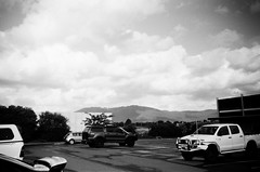Mount Dandenong in the distance (Matthew Paul Argall) Tags: kodakstar500af 35mmfilm ilforddelta100 100isofilm blackandwhite blackandwhitefilm parkinglot parkedcars