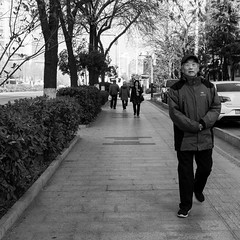 The walker (Go-tea 郭天) Tags: qingdao shandong républiquepopulairedechine cn man portrait alone lonely old wrinkles cap cold winter sunny sun shadow movement sidewalk trees street urban city outside outdoor people candid bw bnw black white blackwhite blackandwhite monochrome naturallight natural light asia asian china chinese canon eos 100d 24mm prime