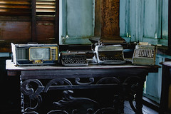 Vintage typewriters and radio on top of steel table (wuestenigel) Tags: silaycity woodenhouse digitalnomad vintage philippines radio historical photographer travel museum photography balaynegrense typewriters history ancestralplace oldhouse walls room zimmer noperson keineperson furniture möbel old alt indoors drinnen seat sitz home zuhause house haus jahrgang retro window fenster family familie wood holz abandoned verlassen chair stuhl container antique antiquität table tabelle architecture diearchitektur interiordesign innenarchitektur