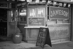 Seattle's Oldest Saloon (sailronin) Tags: seattle pioneersquare saloon signs windows planter sidewalk blackandwhite ilfordfp4 rodinal leicamp 50mmsummicron