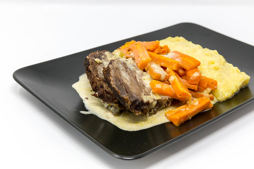 Boiled beef with steamed carrots, mashed potato and sauce on a black plate