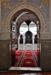 threshold to a holy place (SM Tham) Tags: africa morocco fes medina zaouiaofmoulayidrissii mausoleum sacred holy islam muslim architecture building doorway entrance arch carpet courtyard fountain lamp carvedplaster threshold zellije mosaic art raining wet