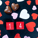 Valentine's date with chocolate and paper hearts on black background