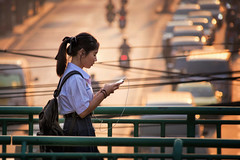 Thai EducAsian (Carl's Captures) Tags: student schoolgirl pedestrian walking walker profile smartphone earbuds backpack bridge traffic railings bokeh urban morning ponytail bangkokthailand victorymonument ratchathewidistrict candid portrait streetphotography streetshooting female southeastasia thai siam asian story nikond7500 sigma18300 photoshopbyfehlfarben thanksbinexo uniform