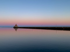 A Slight Tinge of Spring at Sunset (rbodgers) Tags: reflection gradient lighthouse sunset canal spring winter water lake duluth lakesuperior shotoniphone