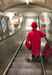 The Queen Visits the Tube? (podmorelarry) Tags: londontube londonunderground queen london escalator pink hat women elderly coat handbag metal solo alone travel streetphotography lady train station transportation