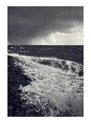 Oosterschelde coming to get me (Photodoos) Tags: monochrome bw zierikzee zeeland oosterschelde rain clouds waves wet dike stones rocks basalt canonnl