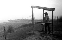 1975: Veere, the iconic view (doc(q)man) Tags: walking hiking pedestrian revolving gate fence dike seadike grass veere walcheren zeeland netherlands bw blackandwhite monochrome seventies 1970s 70s view iconic barbwire mist fog earlyspring sea ocean water silhouette landscape skyline horizon docman