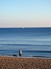 Paseo. (EduOrtÍn.) Tags: mediterráneo mar agua perro hombre catalunya vilanova playa arena velero barco cielo