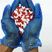 Blue gloved hands holding red and white pills stock photo