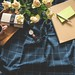 white rose flower bouquet beside brown note, round white analog watch with brown leather band and rectangular brown wooden serving tray on blue and white blanket close-up photo - Credit to https://myfriendscoffee.com/