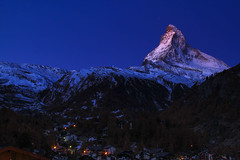 Matterhorn (Zermatt, Switzerland) - early sunlight touching the tip of Matterhorn with twilight sky. (baddoguy) Tags: above alpenglow autumn leaf color beauty in nature below blue clear sky cold temperature image copy space dawn europe european alps famous place focus on foreground horizontal horned international landmark landscape scenery local matterhorn national no people outdoors photography pinnacle peak pyramid shape scenics snow snowcapped mountain sunlight swiss switzerland tip touching tourism town transportation travel destinations twilight valais canton village zermatt