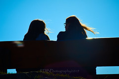 NZ Travels  - Paraparaumu Beach 14 (ArdieBeaPhotography) Tags: twofriends silhouette women woman young glasses long blonde hair blow wind profile bench seat sit together talk dishevelled lateafternoon sunset