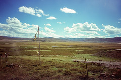 Pole of Prayer Flag (hiphopmilk) Tags: copyright©jaredyehwooehmoehfilms konica offroad 現場監督 zoom 35mm 135film film analog analogue jaredyeh hiphopmilk kodak travel china sichuan aba hongyuan qiongxi qiongxizhen tibetan longrang prayerflags plateau grassland plain sky cloud flags pole