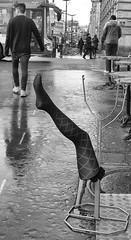 A Kick Up The Aris (tcees) Tags: building bus tables leg stocking crossing wet sky reflection sidewalk bw mono monochrome blackandwhite france man woman people rain lamppost shops ruededunkerque paris x100 fujifilm finepix urban streetphotography street pavement road cycle bike