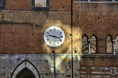 Old walls lit by morning sunlight reflected from cathedral - Piazza Duomo, Siena, Italy. (edk7) Tags: nikond300 nikonnikkor18200mm13556gedifafsvrdx edk7 2008 italy italia tuscany toscana siena piazzaduomo church architecture building oldstructure old stonecarving brick ornamental clock sunlight light reflection window column sculpture arch capital