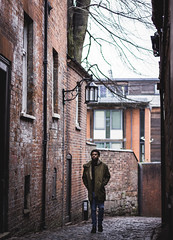 a vision of hope (Qais Nidhal) Tags: portrait person alley brickwall face faded shallow united kingdom uk coventry street pathway old buildings lamp walk walking sudan africa black dark skin cold winter coat afro curly serious hope canon 50mm 600d 14