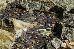 Brother, Can You Spare A Dime? (gecko47) Tags: rock boulder gorge hillside boardwalk capilanosuspensionbridge vancouver britishcolumbia money coins notes scattered thrown loonies toonies nickels quarters dimes wishing tourists change cash silver copper gold currency canadian chinese
