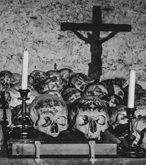 Composed Skulls (jbrad1134) Tags: skulls detail death morbid hallstatt austria travel adventure church catholic painting bw blackandwhite abbey jesus crucifix candles book cemetery grave composition shadows