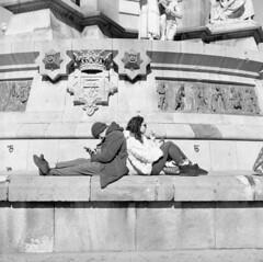 End of Las Ramblas, Barcelona. Film 96011 (richardhunter3) Tags: barcelona yashica 635 tlr ilford hp5 film 120 medium format bw las ramblas street couple monument phones spain girl boy