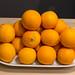 Ungeschälte Orangen gestapelt auf weißer Schale auf Holztisch