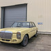 Oldtimer car Mercedes 200D in light yellow stands in front of garage entrance