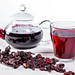 Brewed hibiscus tea in a glass teapot and a Cup with dry hibiscus flowers
