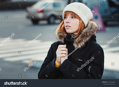 red-haired woman wearing white knitted hat and dressed in warm hooded casual parka jacket outerwear, girl in the parking lot, pedestrian crossing and car in the background, girl warms frozen hands (ig_royal6969) Tags: caucasian hat hood fur woman winter young girl beauty white beautiful cute fashion female people smile cold portrait face lifestyle clothes season attractive lovely coat leisure time background street city style outside holiday wear knitted outfit posing spring hands together frozen warms outdoor black jacket redhaired parking pedestrian crossing crosswalk sale shutterstock