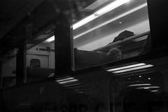 Lone Commuter  (Film) (Harald Philipp) Tags: train rail commuter passenger window dark noir urban railroad reflections kodak retinaiiic ilford delta400 station travel journey street nikoncoolscan 9000ed film blackandwhite analog bw schwarzweis 35mm primelens tourist traveller nocolor monochrome shadows contrast haraldphilipp wanderlust 135film traincarriage lights switzerland europe swisstrains swissrail sbb rangefinder foldingcamera
