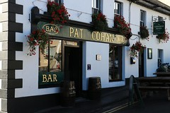 Pat Cohan (RoystonVasey) Tags: canon eos m 1855mm stm zoom eire republic ireland mayo cong village dry canal quiet man conga sarsfield hotel pat cohan bar pub front inn sign flower hanging basket