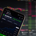 A smartphone displays the Dow 30 market value on the stock exchange