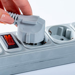 Woman hand plugging in appliance to portable socket thumbnail