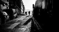 Heading for the horizon. (Mister G.C.) Tags: blackandwhite bw sonya6000 sonyalpha6000 mirrorless streetphotography urbanphotography candid street monochrome photograph image people frombehind silhouette shadows light unposed urban town city sony a6000 35mmf18 sel35f18 35mm primelens schwarzweiss strassenfotografie glasgow scotland europe