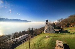 Sunlight on the Church in Vevey, Switzerland (` Toshio ') Tags: toshio vevey switzerland swiss church field mountain lakegeneva lacleman clouds fog alps canon7d 7d religion trees sunlight december winter