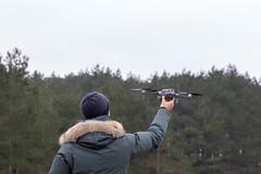 Mann hält Drohne zum Start in die Luft vor Waldstück