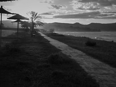 Sunset at Polis Beach (Jonathon Bennett Photos) Tags: polis beach beachfront beauty blackandwhite monochrome nature seascape sunset clouds cloudysky cyprus pebblebeach path track tyre tracks skyclouds skyscape misty mist palmtree grasspath