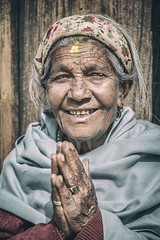 Prayer and Smile (Roberto Pazzi Photography) Tags: asia nepal bhaktapur people portrait street photography place culture one person head shoulders woman elderly nepali ethnicity outdoor wrinkles glance face closeup old eyes nikon buddhist buddhism hands pray religion smile