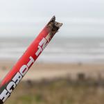 Hand hält abgebrannte Überreste von Silvester-Feuerwerk vor Strand thumbnail