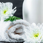 White towel and white chrysanthemums with bottles of cosmetics thumbnail