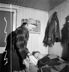 """""""Call boy"""" Doug Watson gives a sleeping brakeman, R.C. LaBelle, notice that his train leaves the terminal in two hours / Le coursier Doug Watson avise le garde-frein ensommeillé, R. C. LaBelle, que son train quittera le terminus dans deux heures (BiblioArchives / LibraryArchives) Tags: lac bac libraryandarchivescanada bibliothèqueetarchivescanada canada sleep beds bed callboy coursier dougwatson breakman gardefrein rclabelle nicholasmorant february1943 février1943 nationalfilmboardofcanada photothèque officenationaldufilmducanada lit lits endormi endormie"""