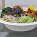 Einwegteller mit Bibimbap Bowl aus Reis mit Soja Chunks, Kimchi, Oshinko und Gemüse an Chilisoße