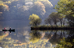 The Fishers: Rydal Water. (trev.eales) Tags: fishing fishermen boat rydalwater rydal trees woodland woods tranquil serene pastoral sunlight autumn autumncolour lake lakedistrict cumbria nationalpark beautiful landscape reflections nikon treveales ngc