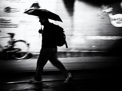 walking in the rain (Sandy...J) Tags: rain urban umbrella walking wall blur olympus monochrom man silhouette street streetphotography sw schwarzweis strasenfotografie city noir fotografie photography blackwhite bw light darkness shadow germany atmosphere mood monochrome movement